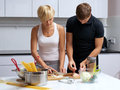 Couple in their kitchen making dinner Royalty Free Stock Photos