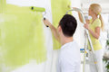 Couple in their new home painting wall green Stock Image