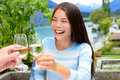 Couple toasting wine glass at outdoor restaurant asian woman cheering with alcohol drink in swiss alps switzerland in summer Royalty Free Stock Photo
