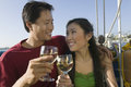 Couple toasting wine glasses on boat smiling the Royalty Free Stock Photo