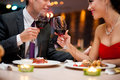 Couple toasting wine glasses hands of their over a restaurant table during a romantic dinner Stock Photos