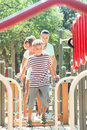 Couple together with teenager overcoming the obstacle course middle aged at playground Stock Image