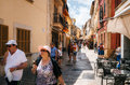 Couple of tourist walking along a street of Alcudia and eat ice-cream, Mallorca Royalty Free Stock Photo