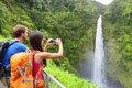 Couple tourists on hawaii by waterfall tourist taking photo pictures of akaka falls waterfall on hawaii big island usa travel Stock Photo