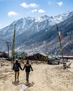 Couple tourists walking on the yellow stone ground to black mountain with snow on the top at Thangu and Chopta valley in winter. Royalty Free Stock Photo