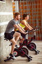 Couple trains on bike in gym Royalty Free Stock Photo