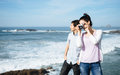 Couple on travel taking photo to beautiful seascape young honeymoon in asturias coast spain with vintage camera Royalty Free Stock Photos