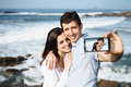 Couple on travel taking smartphone selfie photo young honeymoon in asturias coast spain portrait with camera Stock Photo