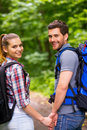Couple traveling with backpacks happy young loving carrying and looking over shoulder smile while walking along the forest pathway Royalty Free Stock Photos