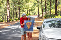 Couple traveling by car in the forest young family sweaters and hats holding paper map la palma island rented Stock Photography