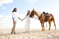 Couple of travellers  holding hands, walking through desert on horse Royalty Free Stock Photo