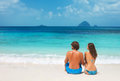 Couple on a tropical beach sitting together beautiful Stock Photo