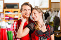Couple is trying Dirndl or Lederhosen in a shop Royalty Free Stock Image