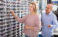 Couple trying spectacles frames and smiling near stand Royalty Free Stock Photo