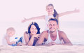 Couple with two children lying on beach