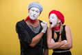 Couple of two funny mimes isolated on background close up horizontal portrait male showing his fist to a female mime wanting to Royalty Free Stock Image