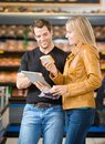 Couple using digital tablet while purchasing meat smiling at butcher s shop Stock Photo