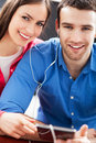 Couple using digital tablet smiling Stock Photos