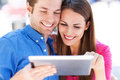 Couple using digital tablet smiling Royalty Free Stock Photography