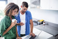 Couple using laptop while having a cup of coffee in kitchen Royalty Free Stock Images