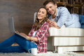 Couple using laptop at home and smiling at camera Royalty Free Stock Photo