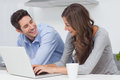 Couple using a laptop in the kitchen beautiful Stock Image