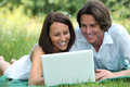 Couple using laptop in park Stock Photo