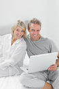 Couple using laptop sitting on bed looking at camera home in bedroom Royalty Free Stock Photos