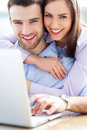 Couple using laptop and smiling Royalty Free Stock Photos