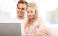 Couple using a laptop and smiling happy young at home Stock Photos