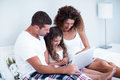 Couple using laptop with their daughter on bed Royalty Free Stock Photo