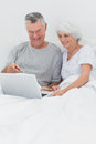 Couple using a laptop together in bed mature Stock Photos