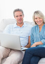 Couple using laptop together on the couch smiling at camera home in living room Stock Photo