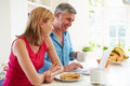 Couple using laptop whilst having breakfast in kitchen searching the web Stock Photography