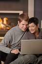 Couple using laptop at winter young hugging on sofa home in computer smiling Stock Photography