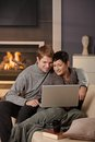 Couple using laptop at winter young hugging on sofa home in computer smiling Stock Images