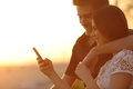 Couple using a smartphone in a sunset back light happy on the beach Royalty Free Stock Images
