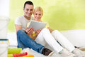 Couple using tablet while painting home young and choosing idea for their Stock Photo