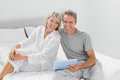 Couple using their digital tablet smiling at camera home in bedroom Royalty Free Stock Images