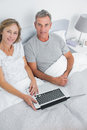 Couple using their laptop together in bed smiling at camera at home bedroom Royalty Free Stock Photos