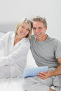Couple using their tablet pc smiling at camera home in bedroom Stock Image