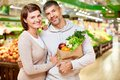 Couple of vegetarians image happy with paperbag full products looking at camera in supermarket Stock Image