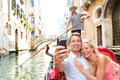 Couple in venice on gondole ride romance boat happy together travel vacation holidays romantic young beautiful taking Stock Images