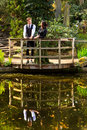 Couple in victorian fashion near lake with reflections in park boy and girl or edwardian vintage clothing the the water on a Royalty Free Stock Images
