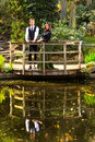 Couple in victorian fashion near lake with reflections in park or edwardian vintage clothing the the water on a lookout over the Stock Images