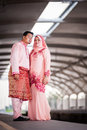 Couple waiting for train at station newly wedded posing railway Stock Photography