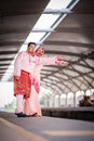 Couple waiting for train at station newly wedded posing railway Stock Image