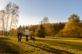 Couple walk dog autumn sunset countryside meadow Royalty Free Stock Photo