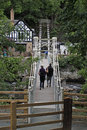 A couple walking across a chainlink bridge people in wales Royalty Free Stock Images
