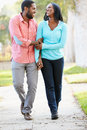 Couple walking along suburban street together smiling to each other Stock Photo